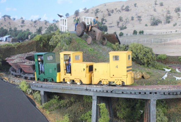 The peace for four Cockatoos feeding on grass seed, is about to be disturbed as Ruston's numbers 4, 5 and 6  (KB Scale models) approach with a ballast train, and the farmer on his tractor is heading down the hill.